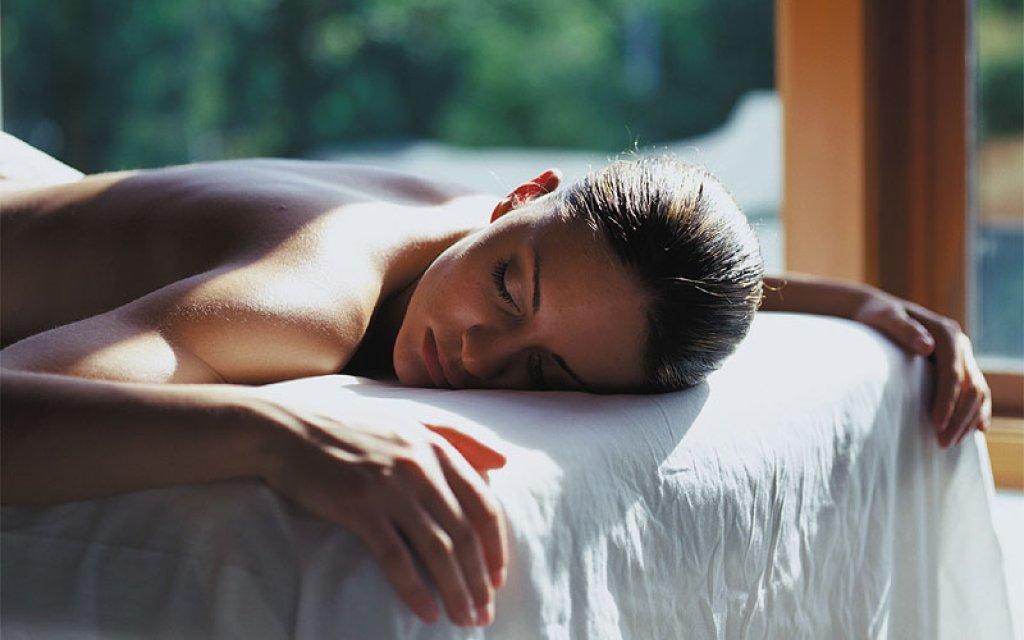 Frau auf einer Liege im Wellnessbereich beim entspannen