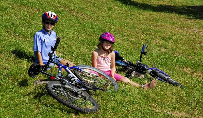 Kinder mit Fahrrad im Gras
