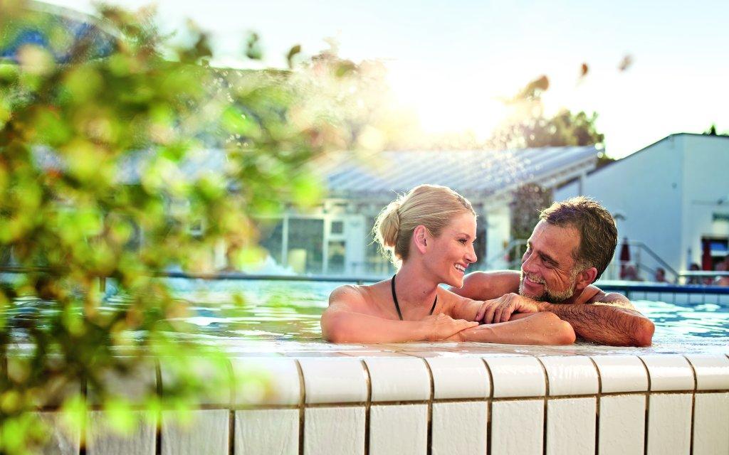 Pärchen am Beckenrand einem Swimmingpools