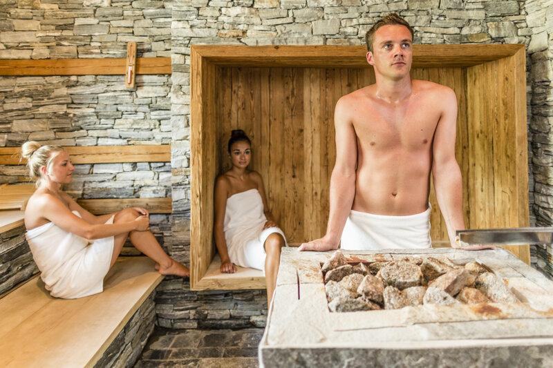 Saunaszene mit Mann am Aufgussofen