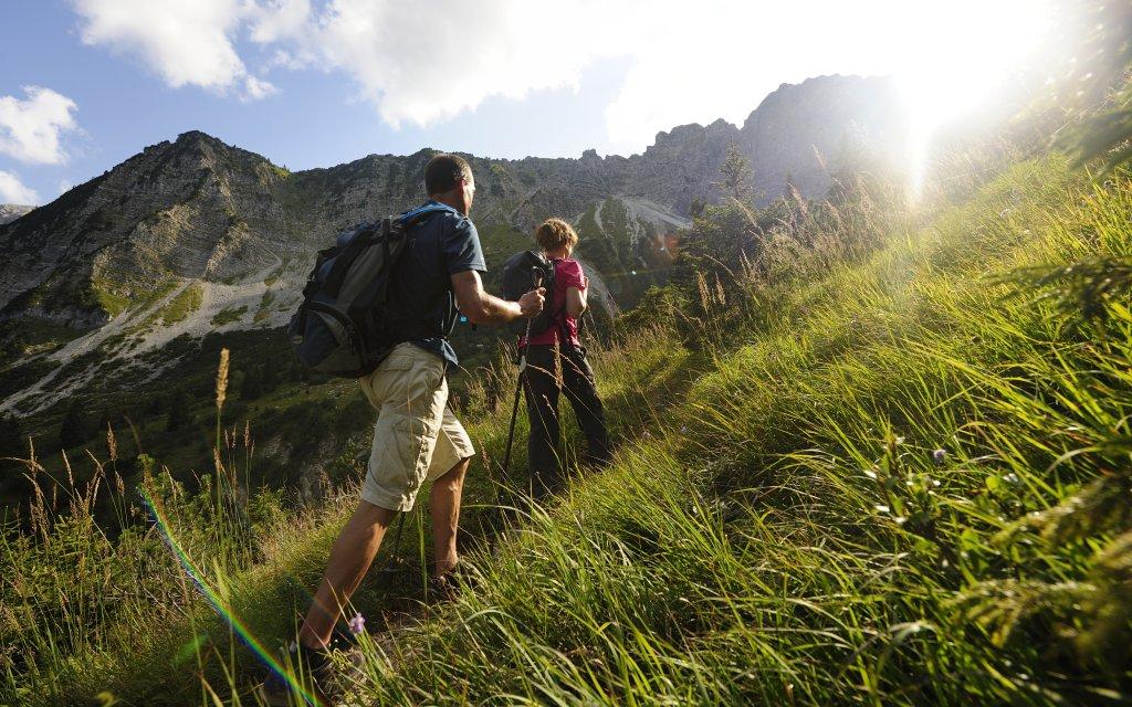 Wanderer in den Alpen gehen der Sonne entgegen