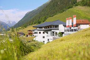 Das Hotel Gipfelherz von außen, im Vordergrund grüne Wiesen, dahinter die Berge