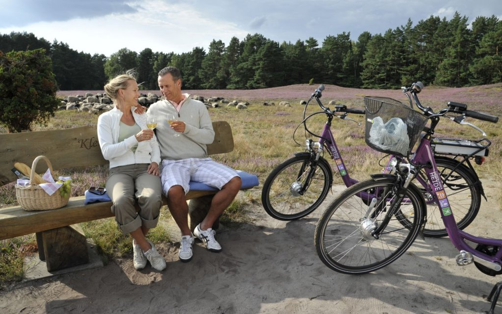 Pärchen beim Picknick auf einer Bank in der Lüneburger Heide