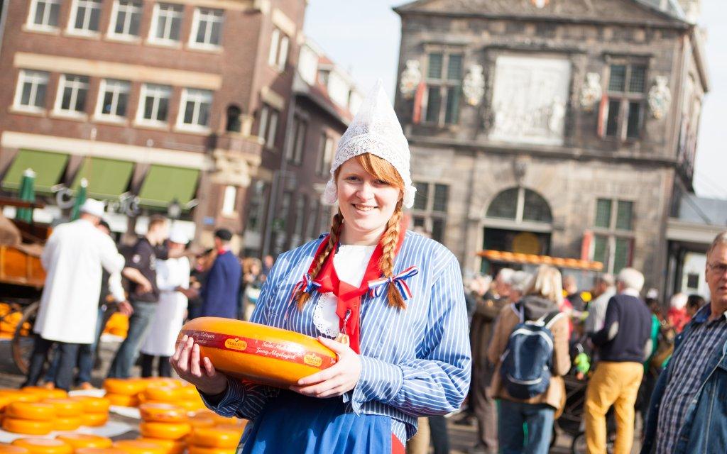 Mädchen in holländischer Tracht mit einem Gouda Käse