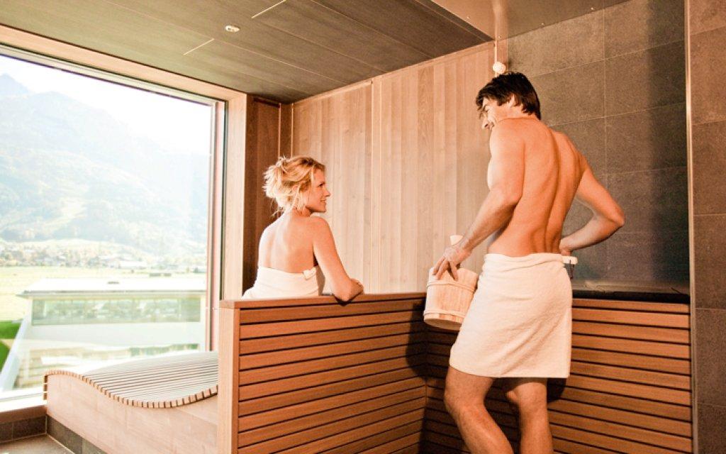 Paar in der Sauna mit Blick auf die Alpen