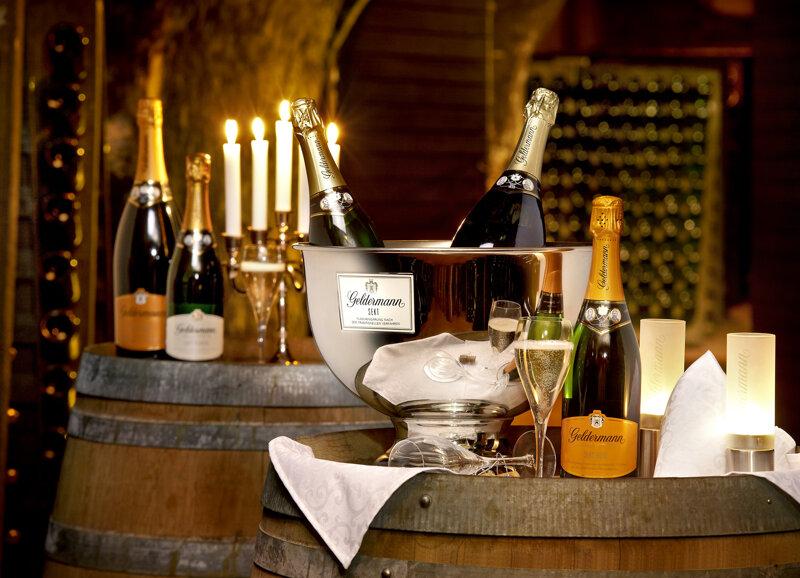Weinflaschen und Sektflaschen auf Weinfässern von Kerzen bestrahlt