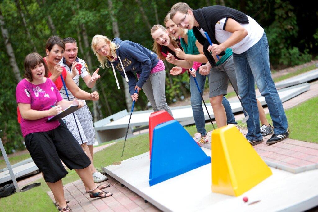 junge Personen beim Minigolf spielen