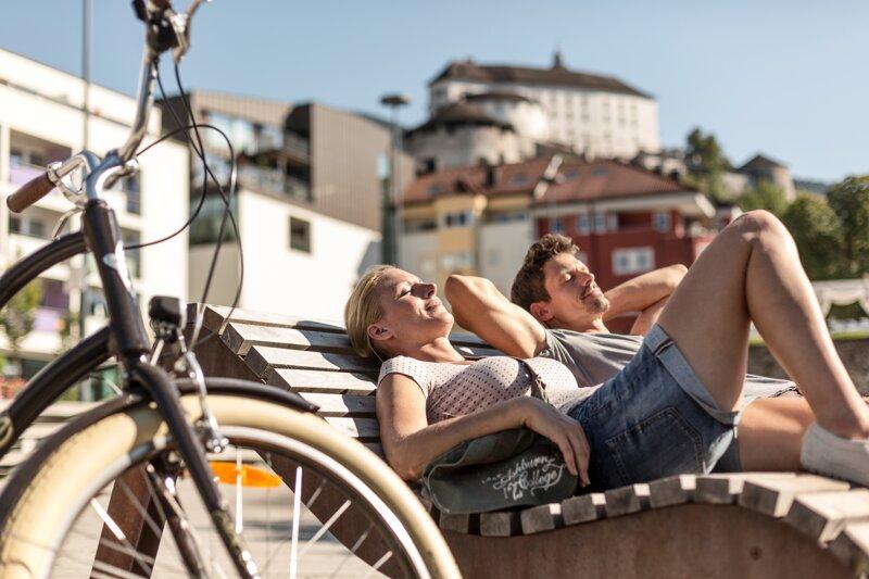 Pärchen ruht sich auf einer Bank vor der Festung Kufstein aus