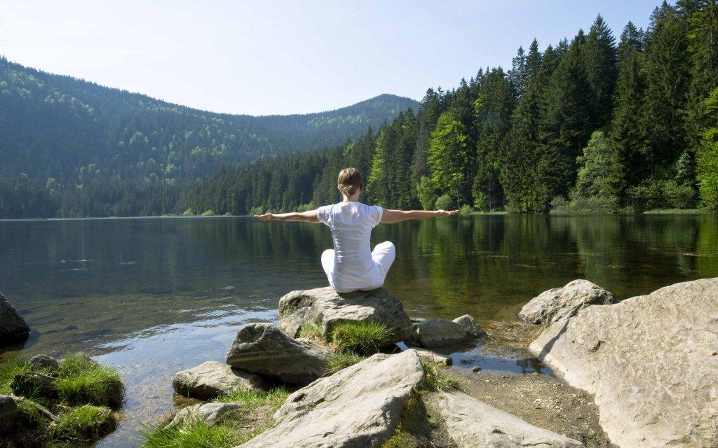 Frau am See meditierend