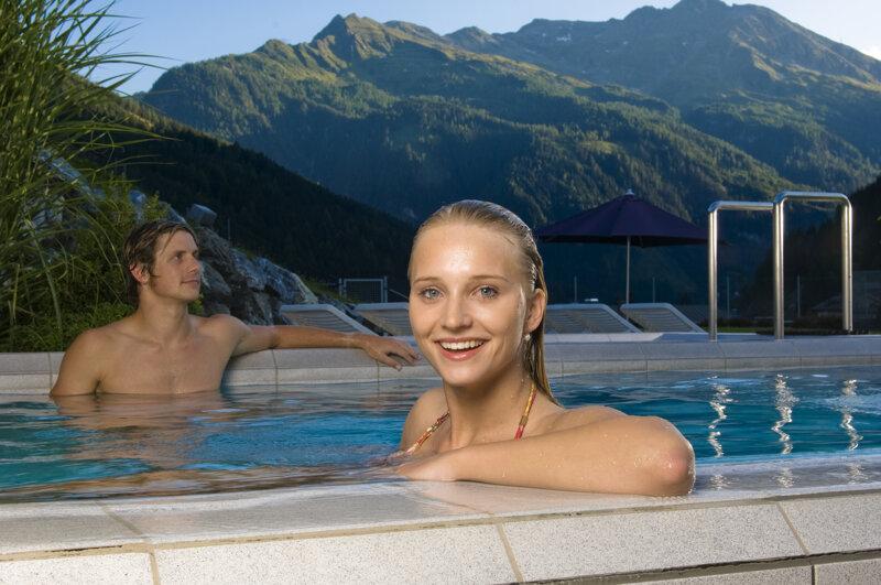 Paar fröhlich im Pool Außenbecken in der Felsentherme Bad Gastein vor Bergen und blauen Himmel