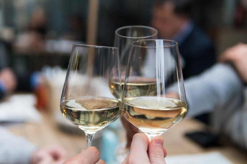 Drei Weingläser anstoßen mit Weißwein
