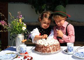 zwei Kinder in Tracht mit Schwarzwälder Kirschtorte