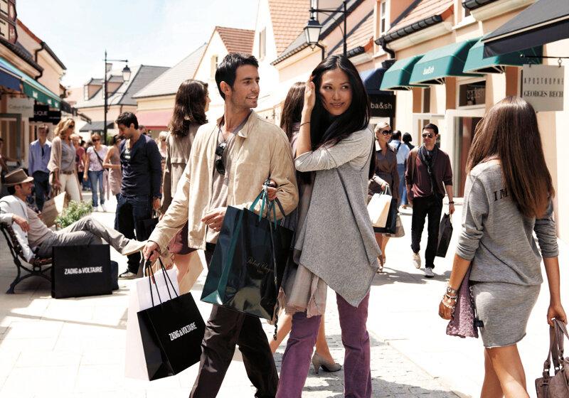 Junges Paar beim einkaufen im Outlet La Vallée Village