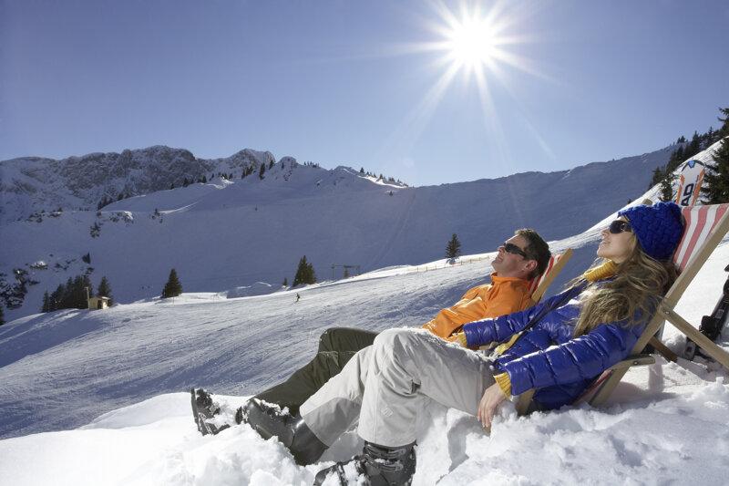 Skifahrer auf Liegestühlen beim Sonne tanken