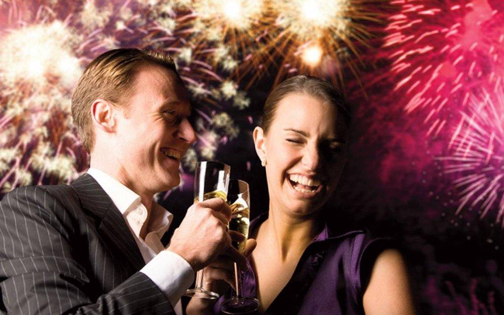 Paar stößt vor Silvesterfeuerwerk an