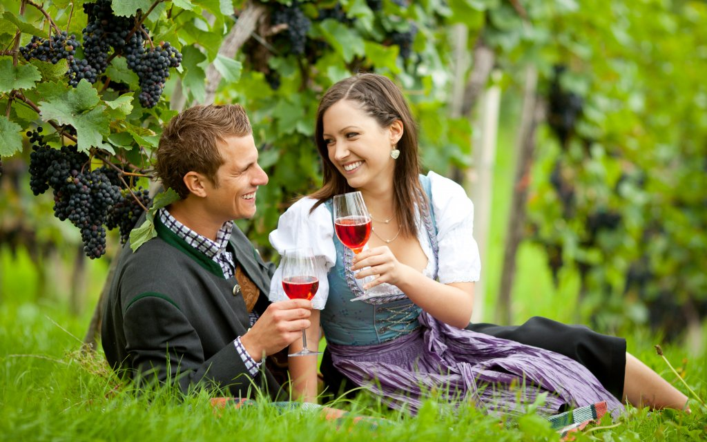Paar trinkt Wein zwischen Weinreben
