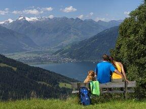 Paar mit Hund auf einer Bank vor Bergen