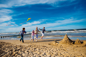 eine Familie lässt Drachen steigen am Strand von Usedom