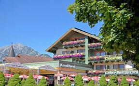 Hotel Christina von außen mit blumengeschmückten Balkonen und Terrasse mit Sonnenschirmen