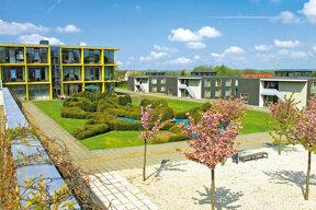 Moderne Außenfassade des Hotels mit Gartenanlage und Bäumen