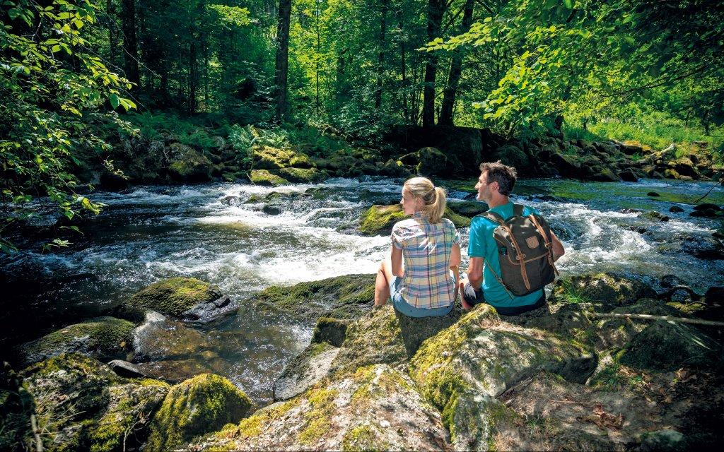 Paar an einem Bach im Bayerischen Wald