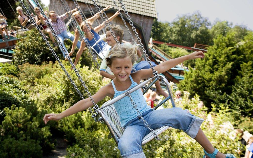 Kind im Kettenkarussell im Freizeitpark Slagharen