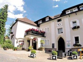 Außenansicht des Hotels Post in Oberbozen mit Palme, Buchsbäumen und bunten Balkonblumen