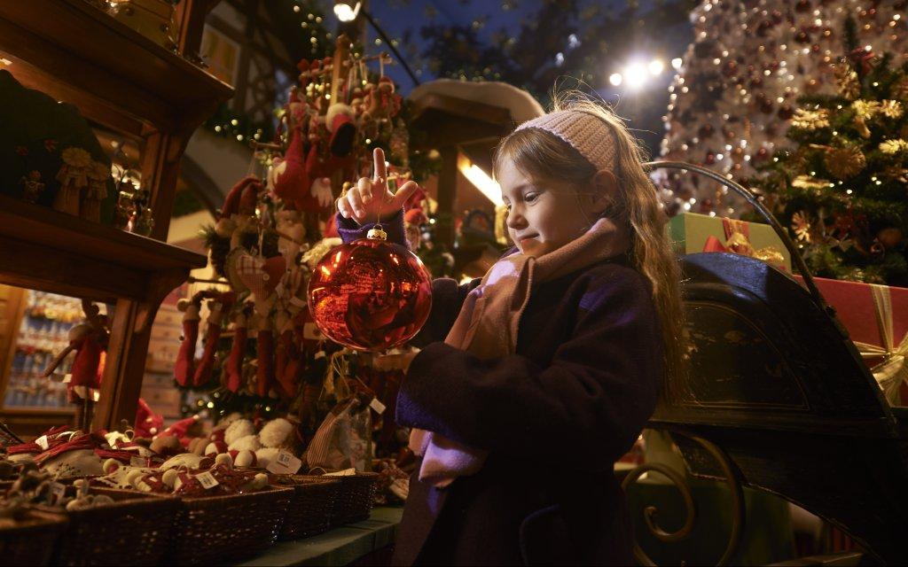 Kind mit Christbaumschmuck auf einem Weihnachtsmarkt in Bayern