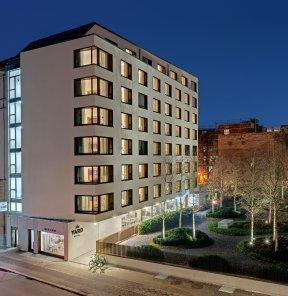 Beleuchtetes the Yard Hotel in Kreuzberg in der Nacht.