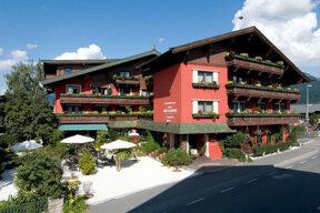 Rote Außenfassade des Hotels Bruggwirt mit blumengeschmückten Balkonen