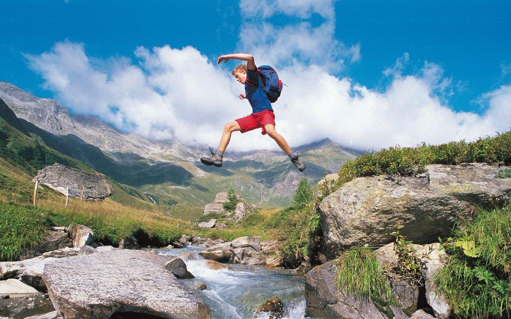 Mann springt über einen Gebirgsbach