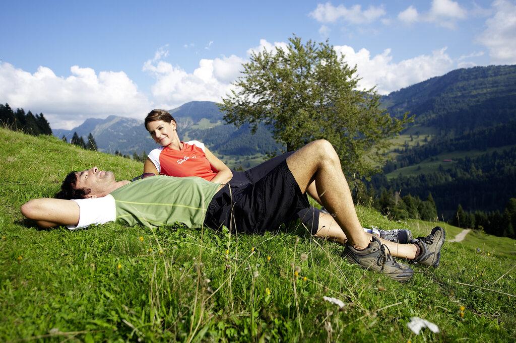 Paar relaxt auf einer Wiese im Allgäu