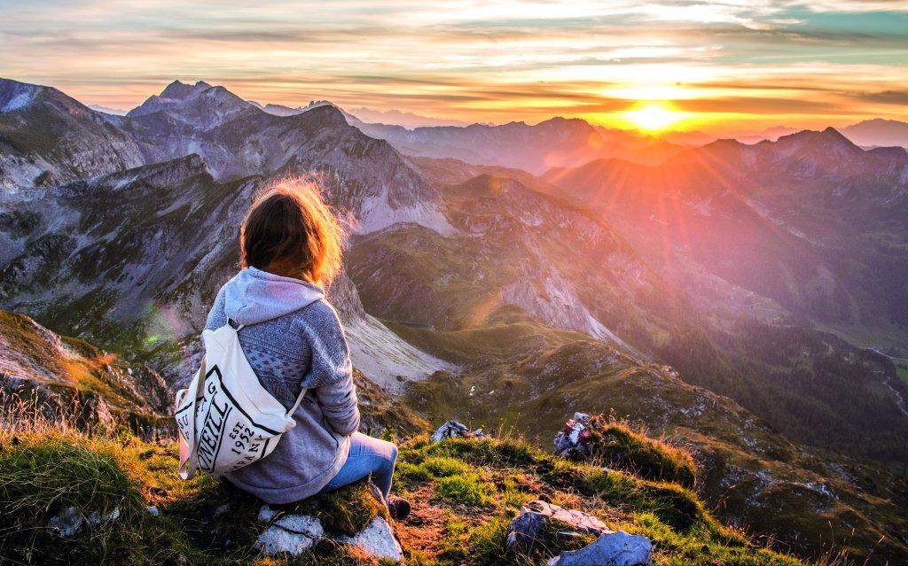 Frau betrachtet Sonnenuntergang in Obertauern