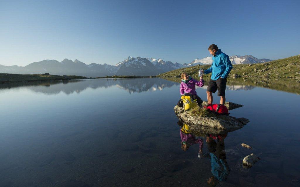 Paar macht eine Wanderpause vor einem See im Ötztal