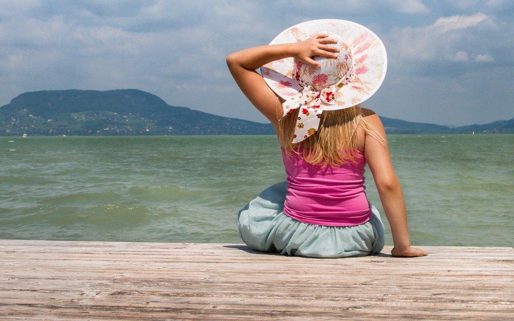 Mädchen mit Hut blickt auf den Plattensee in Ungarn