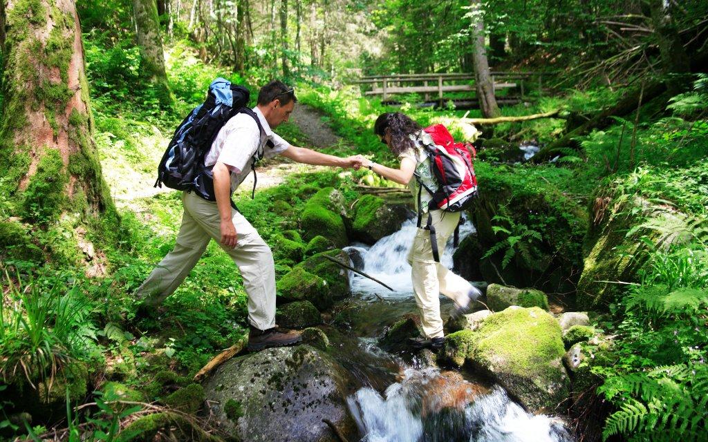 Wanderer überqueren einen Bach im Schluchtensteig Schwarzwald