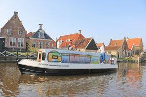 Elektro-Hausboot vor Häuserzeile in Friesland