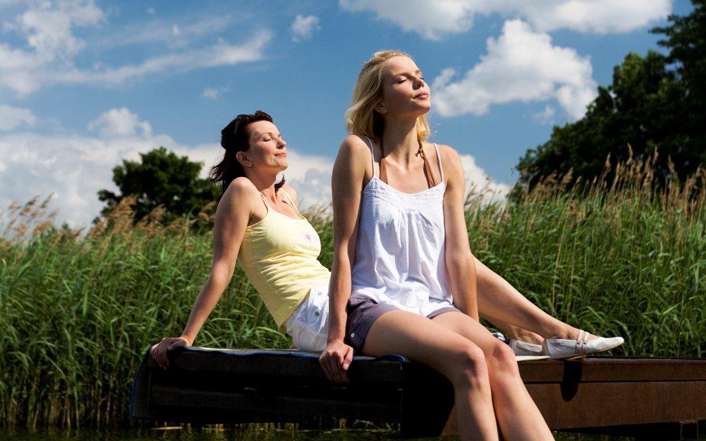 Zwei Frauen entspannen auf einen Steg am Wasser