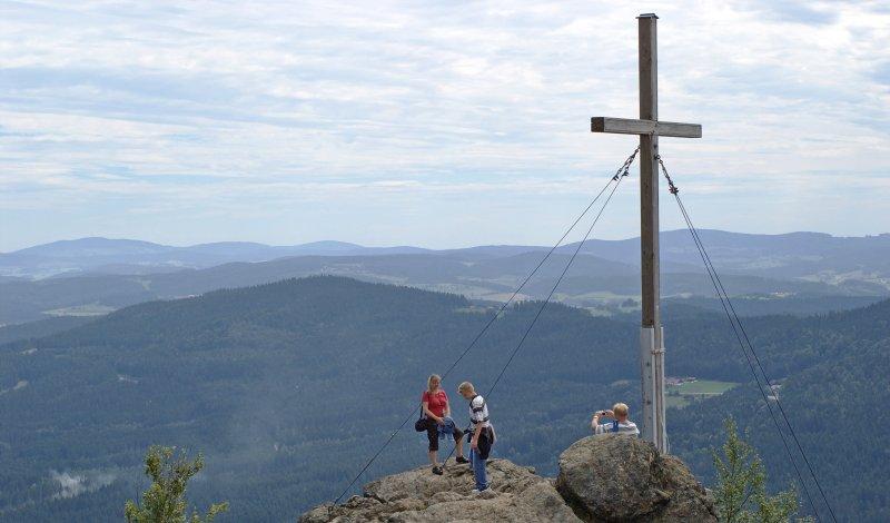 Wanderer am Gipfelkreuz auf dem Silberberg