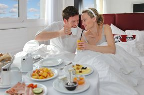 Liebespaar genießt Frühstück im Hotelbett