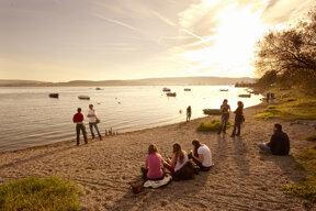 Menschen am Sandufer des Bodensees