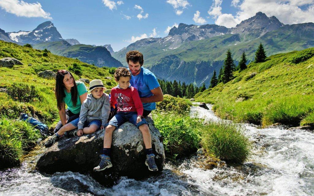 Familie in einem Bach in Graubünden