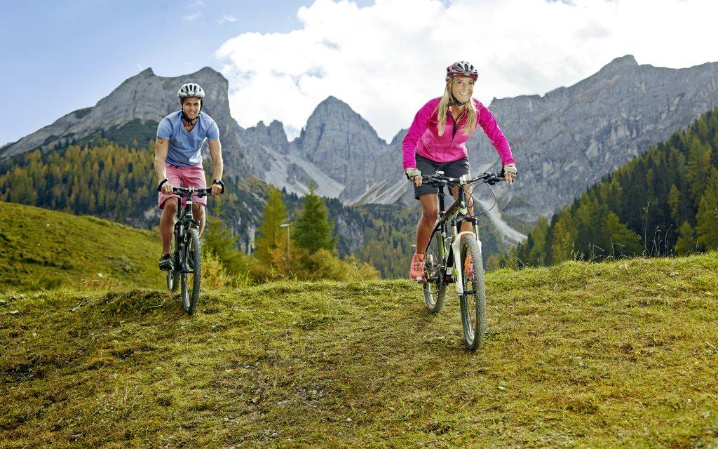 Paar fährt Mountainbike in den Bergen