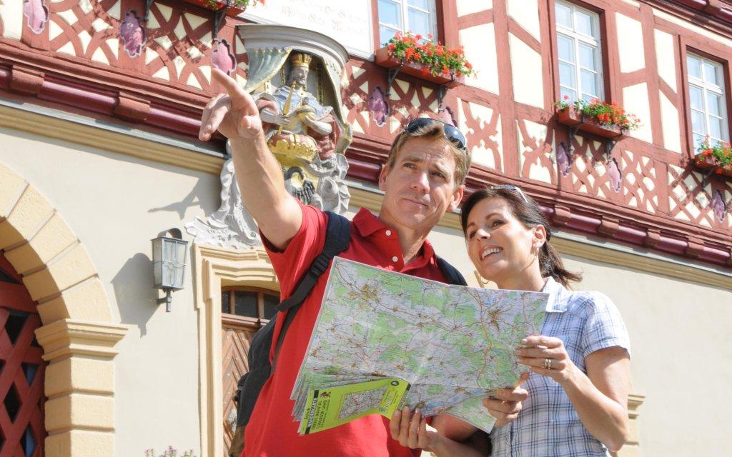 Urlauber mit Stadtplan vor dem Rathaus Bad Staffelstein