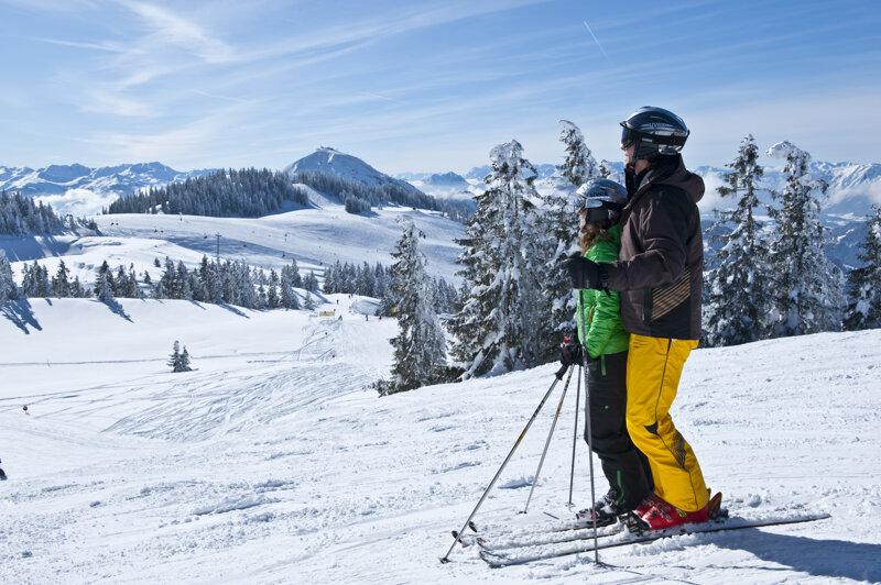 Skifahrer genießen den Blick auf die Gipfel und Pisten des Wilden Kaisers
