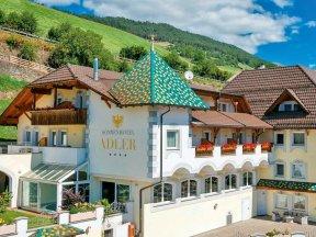 Außenaufnahme des Sonnenhotels Adler in Villanders mit Liegewiese und Terrasse