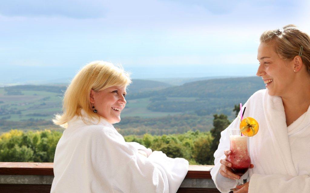 Zwei Frauen im Bademantel vor der Aussicht auf die Rhön