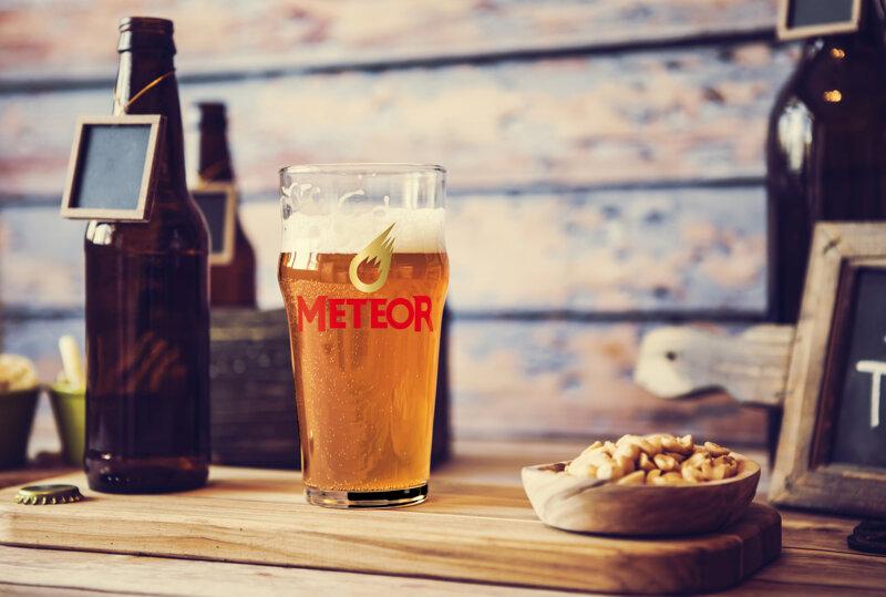 Brettchen mit Bierflasche, Glas mit Meteor-Aufschrift und Nüssen
