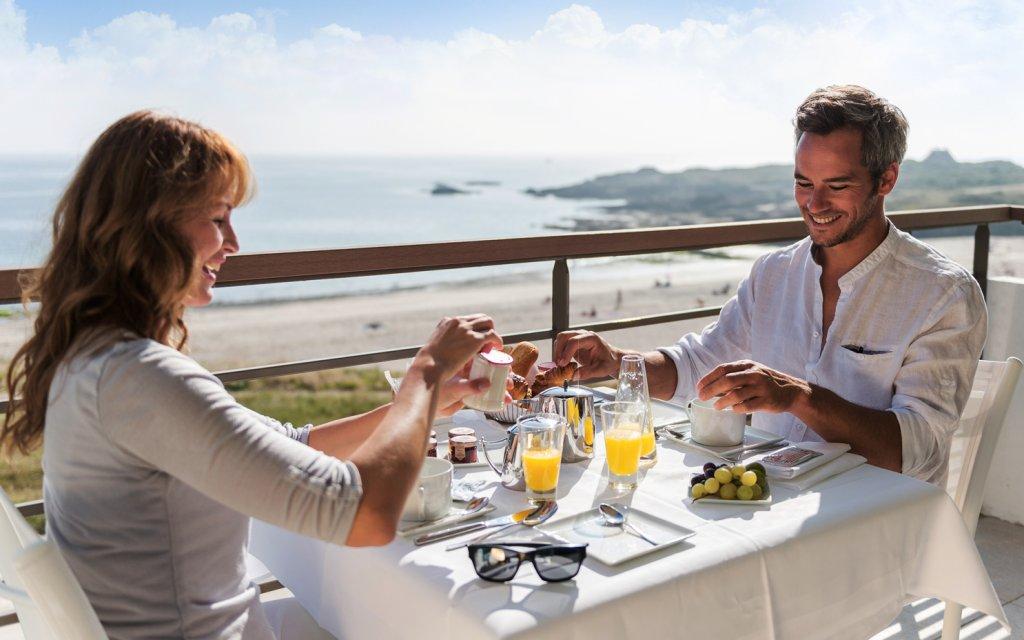 Pärchen beim Frühstück mit Blick aufs Meer
